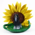 Afghan Hound Black Figurine Sitting on a Green Leaf in Front of a Yellow Sunflower