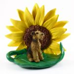 Airedale Figurine Sitting on a Green Leaf in Front of a Yellow Sunflower