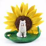 American Eskimo Figurine Sitting on a Green Leaf in Front of a Yellow Sunflower