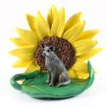 Australian Cattle Dog Blue Figurine Sitting on a Green Leaf in Front of a Yellow Sunflower