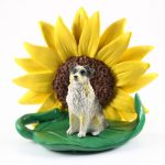 Australian Shepherd Blue Docked Figurine Sitting on a Green Leaf in Front of a Yellow Sunflower