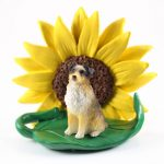 Australian Shepherd Brown Docked Tail Figurine Sitting on a Green Leaf in Front of a Yellow Sunflower