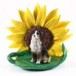 Australian Shepherd Tri Color Figurine Sitting on a Green Leaf in Front of a Yellow Sunflower
