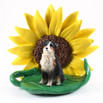 Australian Shepherd Tri Color Docked Tail Figurine Sitting on a Green Leaf in Front of a Yellow Sunflower