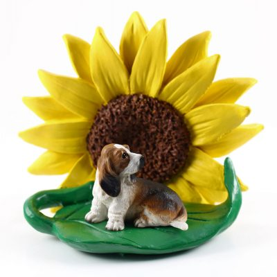 Basset Hound Figurine Sitting on a Green Leaf in Front of a Yellow Sunflower
