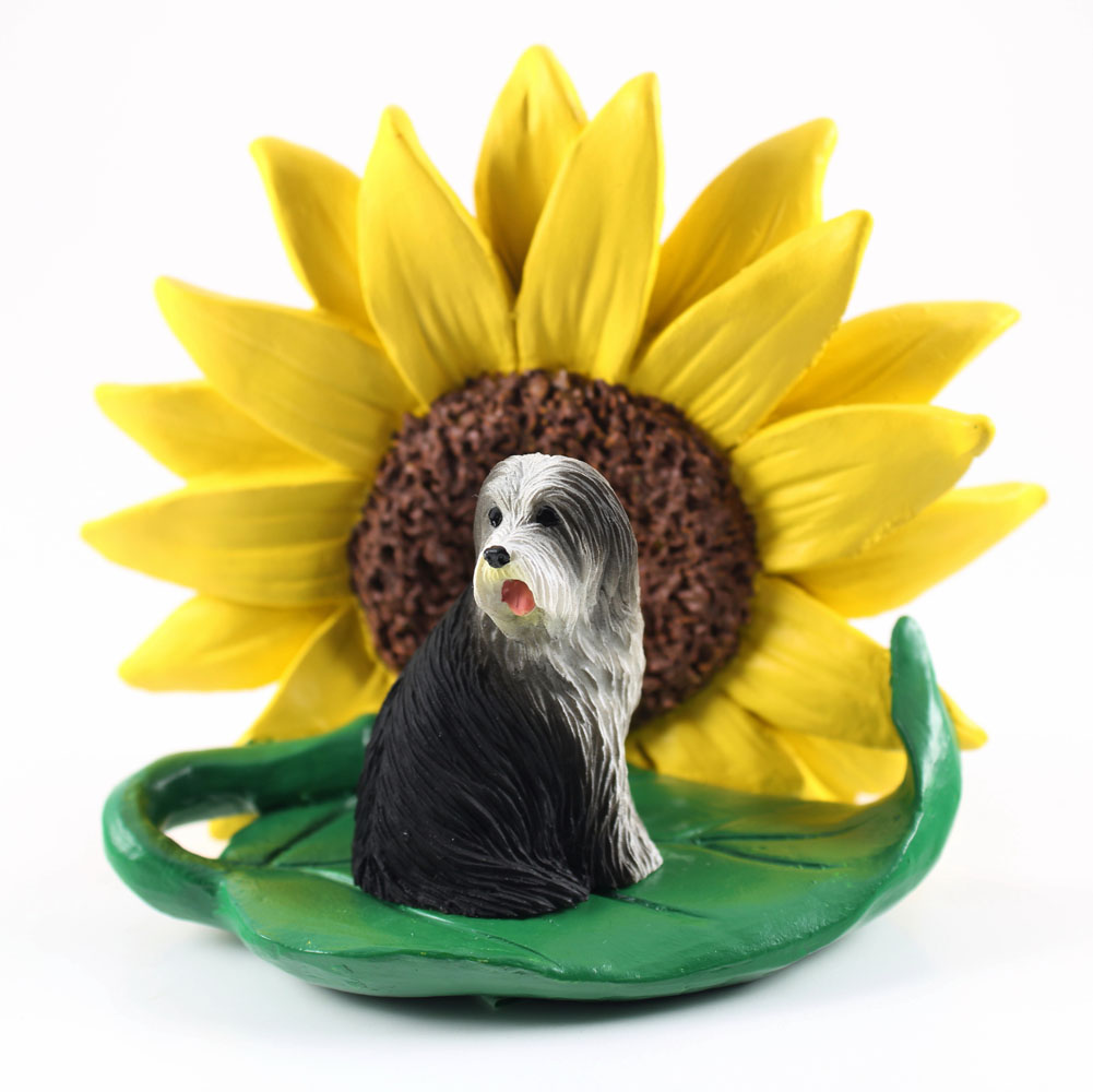 Bearded Collie Figurine Sitting on a Green Leaf in Front of a Yellow Sunflower