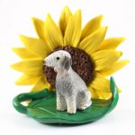 Bedlington Terrier Figurine Sitting on a Green Leaf in Front of a Yellow Sunflower