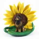 Belgian Tervuren Figurine Sitting on a Green Leaf in Front of a Yellow Sunflower
