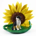 Bernese Mountain Dog Figurine Sitting on a Green Leaf in Front of a Yellow Sunflower