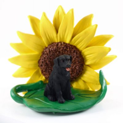 Black Lab Figurine Sitting on a Green Leaf in Front of a Yellow Sunflower