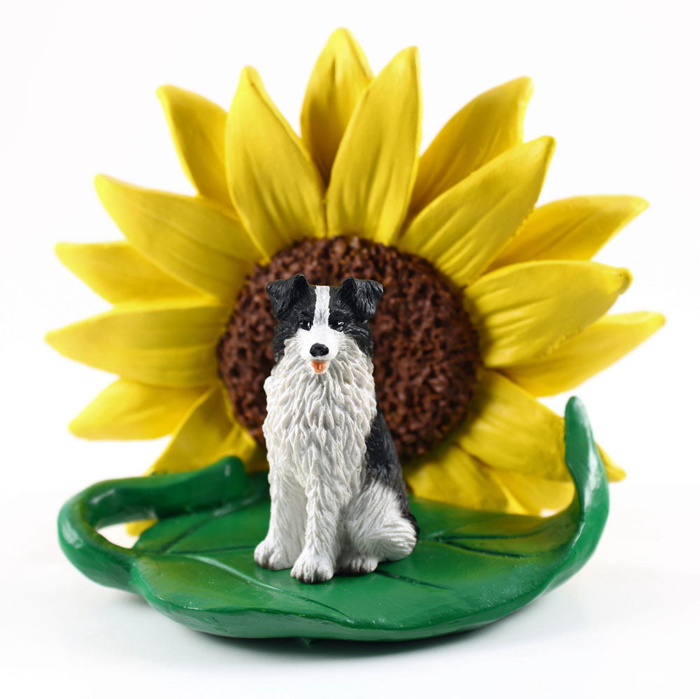 Borrder Collie Figurine Sitting on a Green Leaf in Front of a Yellow Sunflower