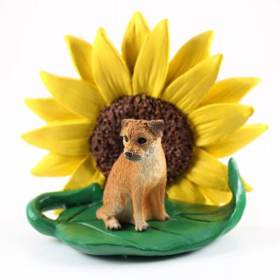 Border Terrier Figurine Sitting on a Green Leaf in Front of a Yellow Sunflower