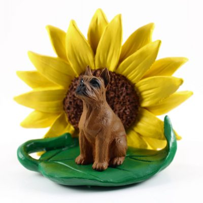 Boxer Tawny Figurine Sitting on a Green Leaf in Front of a Yellow Sunflower