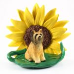 Briard Figurine Sitting on a Green Leaf in Front of a Yellow Sunflower