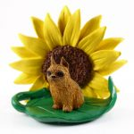 Brussels Griffon Red Figurine Sitting on a Green Leaf in Front of a Yellow Sunflower