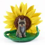 Cairn Terrier Brindle Figurine Sitting on a Green Leaf in Front of a Yellow Sunflower