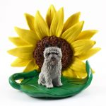 Cairn Terrier Gray Figurine Sitting on a Green Leaf in Front of a Yellow Sunflower