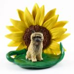 Cairn Terrier Red Figurine Sitting on a Green Leaf in Front of a Yellow Sunflower