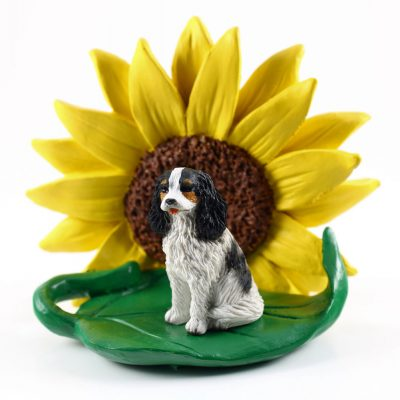 Cavalier King Charles Black/White Figurine Sitting on a Green Leaf in Front of a Yellow Sunflower