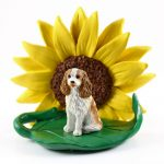 Cavalier King Charles Brown/White Figurine Sitting on a Green Leaf in Front of a Yellow Sunflower