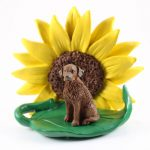 Chesapeake Bay Retriever Figurine Sitting on a Green Leaf in Front of a Yellow Sunflower