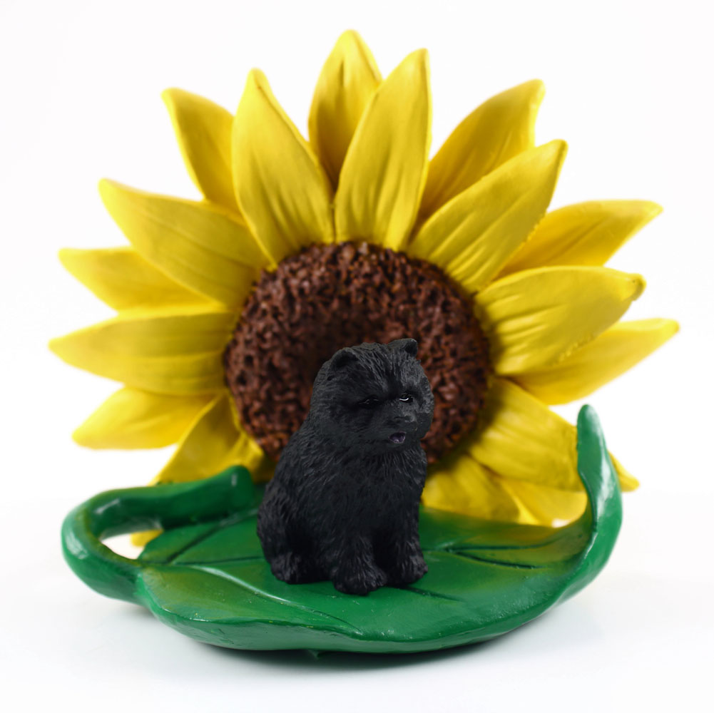 Chow Chow Black Figurine Sitting on a Green Leaf in Front of a Yellow Sunflower