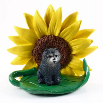 Chow Chow Blue Figurine Sitting on a Green Leaf in Front of a Yellow Sunflower