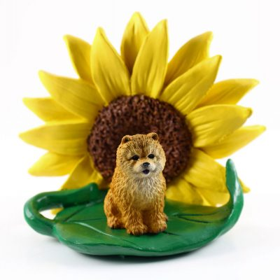 Chow Chow Red Figurine Sitting on a Green Leaf in Front of a Yellow Sunflower