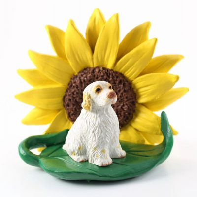Clumber Spaniel Figurine Sitting on a Green Leaf in Front of a Yellow Sunflower