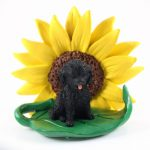 Cockapoo Black Figurine Sitting on a Green Leaf in Front of a Yellow Sunflower