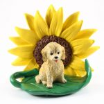 Cockapoo Blonde Figurine Sitting on a Green Leaf in Front of a Yellow Sunflower