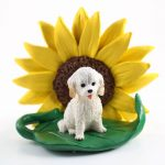 Cockapoo White Figurine Sitting on a Green Leaf in Front of a Yellow Sunflower