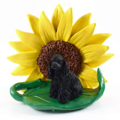Cocker Spaniel Black Figurine Sitting on a Green Leaf in Front of a Yellow Sunflower