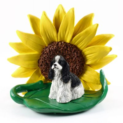 Cocker Spaniel Black/White Figurine Sitting on a Green Leaf in Front of a Yellow Sunflower