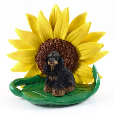 Cocker Spaniel Black/Brown Figurine Sitting on a Green Leaf in Front of a Yellow Sunflower