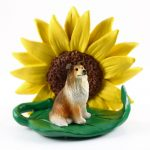 Collie Sable Figurine Sitting on a Green Leaf in Front of a Yellow Sunflower
