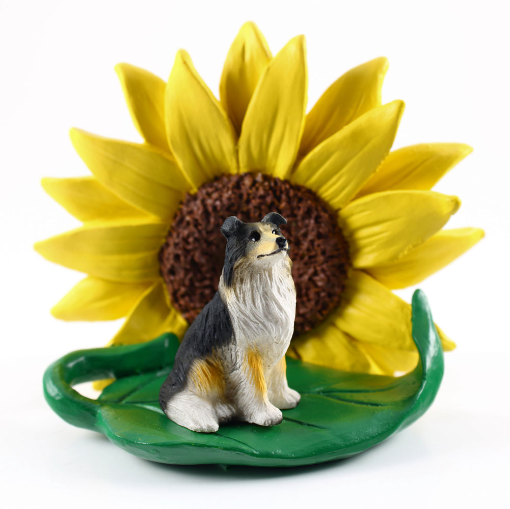 Collie Tri Color Figurine Sitting on a Green Leaf in Front of a Yellow Sunflower
