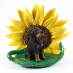 Coonhound Black/Tan Figurine Sitting on a Green Leaf in Front of a Yellow Sunflower