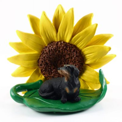 Dachshund Black Figurine Sitting on a Green Leaf in Front of a Yellow Sunflower