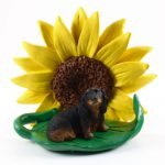 Dachshund Black Long Hair Figurine Sitting on a Green Leaf in Front of a Yellow Sunflower