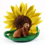 Dachshund Red Long Hair Figurine Sitting on a Green Leaf in Front of a Yellow Sunflower