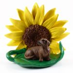 Dachshund Red Figurine Sitting on a Green Leaf in Front of a Yellow Sunflower