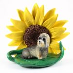 Dandie Dinmont Figurine Sitting on a Green Leaf in Front of a Yellow Sunflower