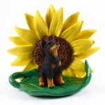 Doberman Pinscher Black Figurine Sitting on a Green Leaf in Front of a Yellow Sunflower
