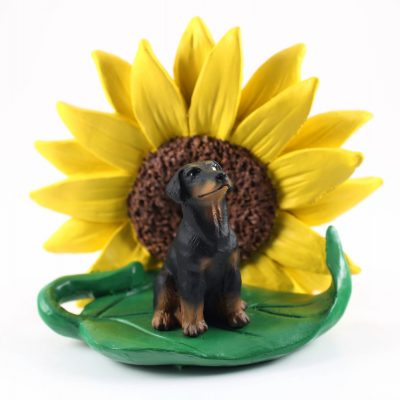 Doberman Pinscher Black Uncropped Figurine Sitting on a Green Leaf in Front of a Yellow Sunflower