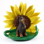 Doberman Pinscher Red Figurine Sitting on a Green Leaf in Front of a Yellow Sunflower