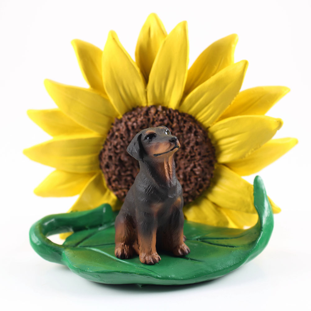 Doberman Pinscher Red Uncropped Figurine Sitting on a Green Leaf in Front of a Yellow Sunflower
