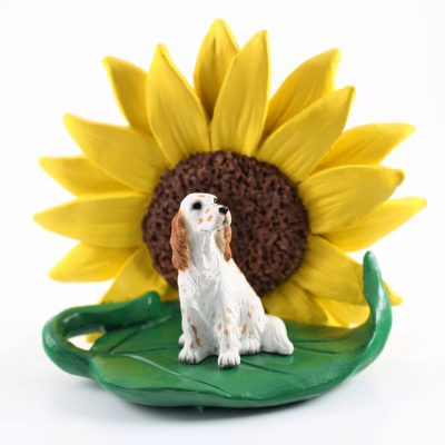 English Setter Orange Figurine Sitting on a Green Leaf in Front of a Yellow Sunflower