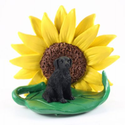 Flat Coated Retriever Figurine Sitting on a Green Leaf in Front of a Yellow Sunflower