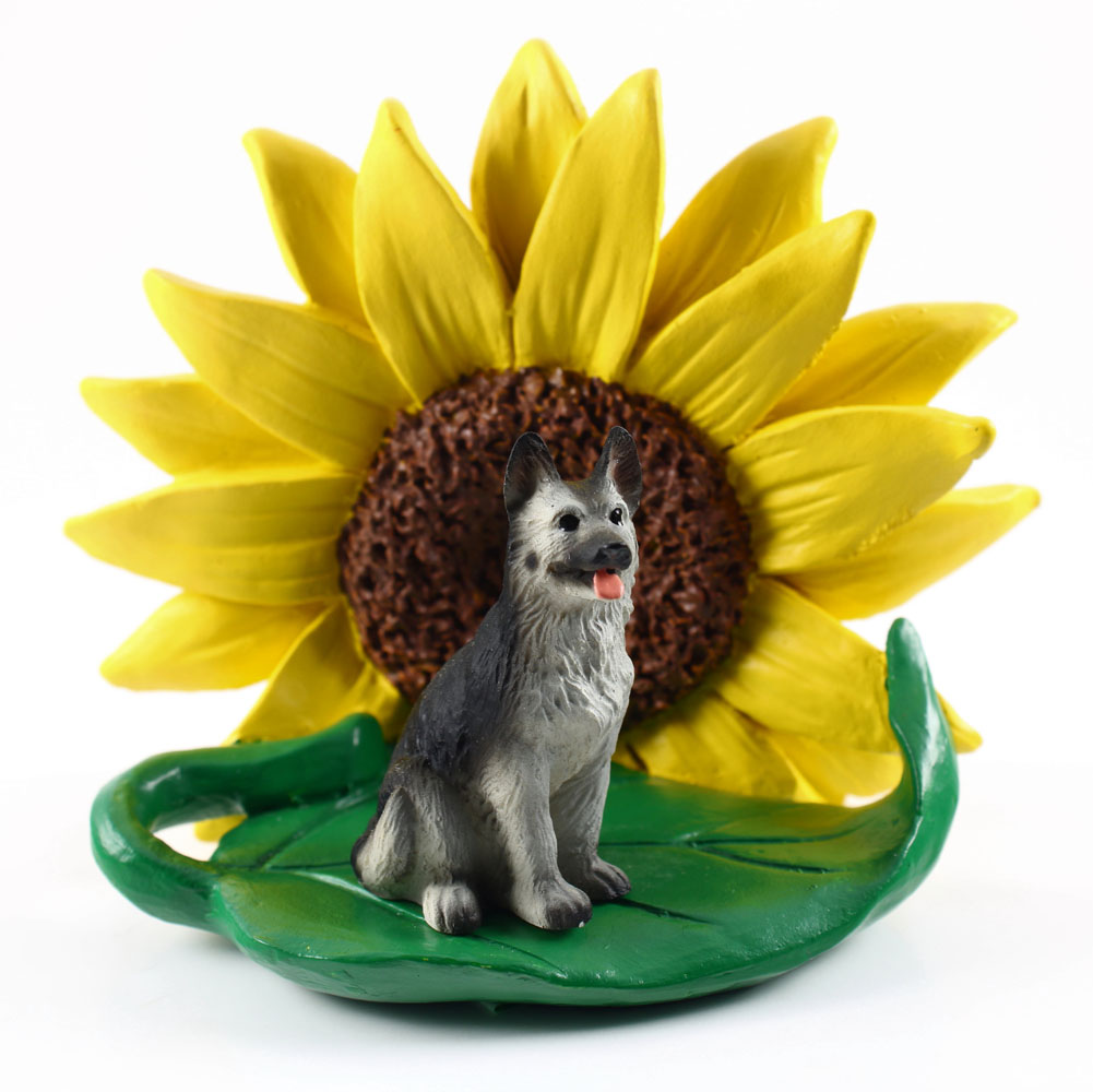 German Shepherd Black/Silver Figurine Sitting on a Green Leaf in Front of a Yellow Sunflower